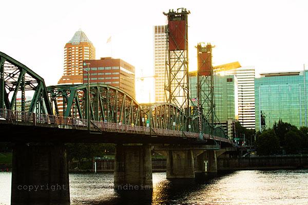 Sunset through Portland city buildings over Hawthorne Bridge by photographer Angie Windheim.